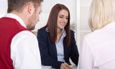 Consultation with young attractive couple at office. — Stock Photo