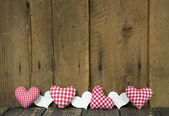 Wooden board decorated with checked hearts for a greeting card. — ストック写真