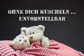 Two beige teddy bears in love lying in bed - concept for love. — Stock Photo