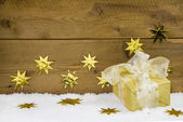 Gold christmas gift on snow and gold stars on wooden background. — Foto Stock