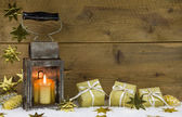 Metal lantern with wrapped gold presents and stars. — Stock Photo