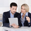 Senior female managing director with assistant looking at digital tablet. — Stock Photo