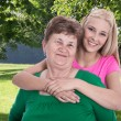 Older woman with her granddaughter or daughter in garden. — Stock Photo
