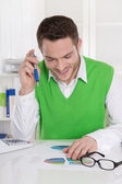 Successful smiling business man sitting at desk. — Stock Photo
