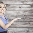 Smiling businesswoman over wodden background presenting. — Stock Photo
