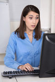 Amazed business woman looking amazed in her computer. — Stock Photo