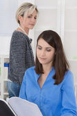 Bullying at work: older business woman is jealous. — Zdjęcie stockowe