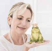Single attractive older woman with a frog king in her hands. — Stockfoto