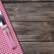 Knife and fork in red white checkered on wooden background. — Stock Photo