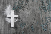 White cross with feather on an old rustic background. — Stock Photo