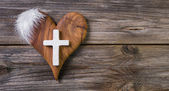 Wooden background with olive heart and white cross for an obitua — Stock Photo