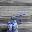 Gift box with blue checked ribbon on wooden grey background. — Stock Photo #46483147