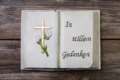Mourning: cross and german text on a book of stone. — Stock Photo