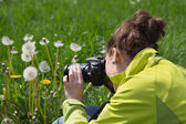 Young woman in leisure time making nature photos in the grass. — Stock Photo