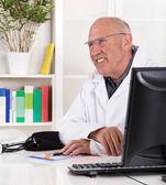 Портрет старше врач с опытом улыбается. — Стоковое фото