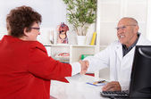 Handshake: Portrait of an older doctor with experience with pati — Stock Photo