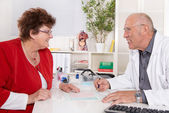 Portrait of an older doctor talking with a female patient. — Stock Photo