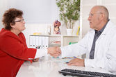 Appointment at doctor: older woman talking with a specialist. — Stock Photo
