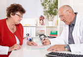 Portrait: older doctor with experience talking with senior woman — Stock Photo