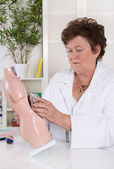 Senior female doctor demonstrate and explain the human body. — Stock Photo