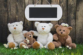 Happy teddy bear team on wooden background for a greeting card w — Stock Photo