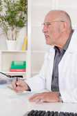 Portrait of an older male doctor sitting at desk. — Stock Photo