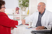 Shaking hands at doctors office with his senior patient. — Stock Photo