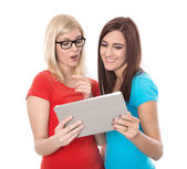 Two young isolated woman looking at tablet-pc: concept for datin — Stock Photo