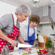 Grandmother with grandson in the kitchen preparing roast meat. — Stock fotografie #48820621