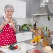 Older happy woman eating yoghurt in the morning. — Stock Photo #48821147