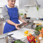 Happy senior woman in the kitchen preparing fresh fish. — Stock Photo #48821823
