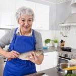 Happy senior woman in the kitchen preparing fresh fish. — Stock Photo #48821863