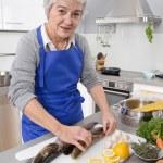 Happy senior woman in the kitchen preparing fresh fish. — Stock Photo #48821881