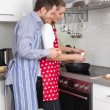 Young fresh married couple in the kitchen cooking together fried — Stock Photo