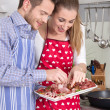 Young fresh married couple in the kitchen eating sausages. — Stock Photo #48821911