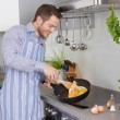 Young man in the kitchen cooking fried eggs. — Stock Photo #48822047