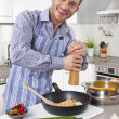 Young man in the kitchen cooking fried eggs. — Stock Photo #48822185