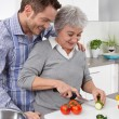 Young man and older woman cooking together in the kitchen. — Stock Photo #48822245
