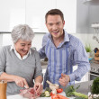 Hotel mama: young man and older woman cooking together pork. — Stock Photo #48822341