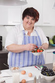 Overweight and smiling woman making breakfast. — Stock Photo
