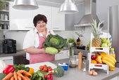Chubby smiling woman in the kitchen making diet. — Foto de Stock