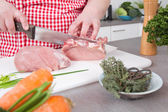 Woman in the kitchen cooking roast pork: cutting meat. — Stock Photo