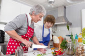 Grandmother with grandson in the kitchen preparing roast meat. — Stock Photo