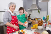 Happy family: Grandmother and grandson cooking together. — Stock Photo