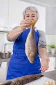 Happy senior woman in the kitchen preparing fresh fish. — Stok fotoğraf