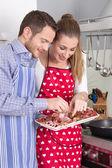 Junge frisch verheiratet paar in der Küche Essen Würstchen. — Stockfoto