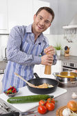 Young man in the kitchen cooking fried eggs. — Stok fotoğraf