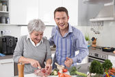Hotel mama: young man and older woman cooking together pork. — Stock Photo