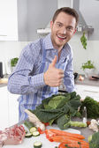 Man in the kitchen with thumb up preparing dinner. — Stock Photo