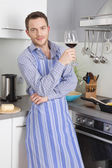 At the end of work: single man drinking glass of wine in the kit — Stock Photo